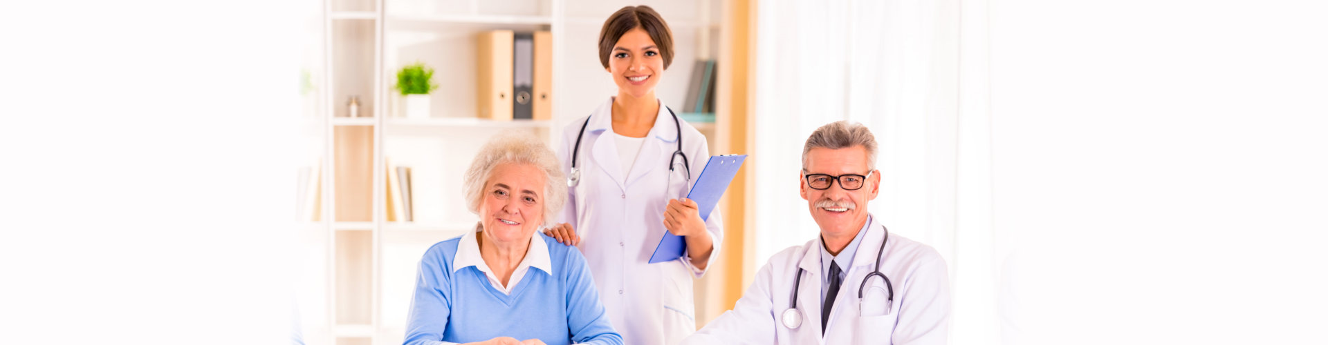 medical professionals with senior patient smiling